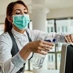 ppe thumbnail.jpg (Businesswoman with face mask disinfecting desktop PC...